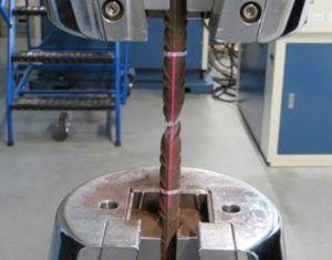 Zdjęcie wykonane podczas przeprowadzania statycznej próby rozciągania stali – pręta zbrojeniowego z wykorzystaniem ekstensometru bezkontaktowego (laserowego)